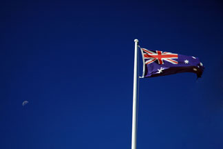 Australia flag flying with a deep blue sky background