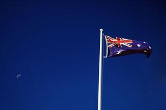 Australia flag flying with a deep blue sky background